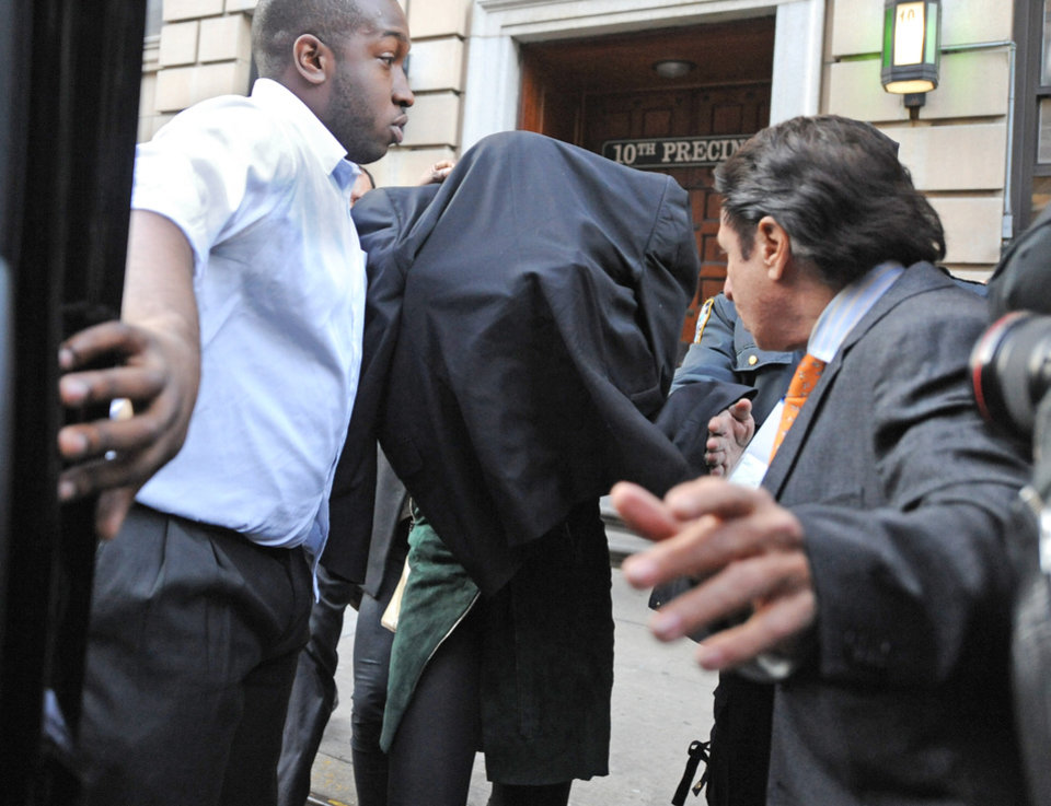 Photo - Lindsay Lohan, center, is escorted from the 10th Precinct police station, with her face shielded, Thursday, Nov. 29, 2012, in New York after being charged for allegedly striking a woman at a nightclub. Police say Lohan was arrested at 4 a.m. and charged with third-degree assault. They say she got into the argument with another woman at Club Avenue in Manhattan and struck the woman in face with her hand. (AP Photo/ Louis Lanzano)
