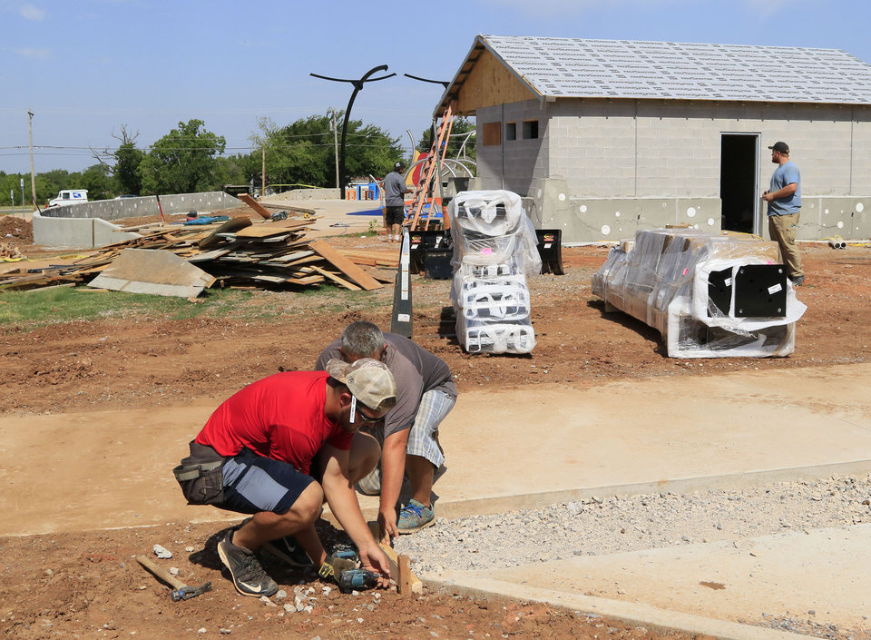 Photo -  Workers continue to work at the site of Edmond's only splash pad. City officials said they are frustrated the project has been delayed, closing the splash pad so far this summer. [PHOTO BY PAUL HELLSTERN, THE OKLAHOMAN]