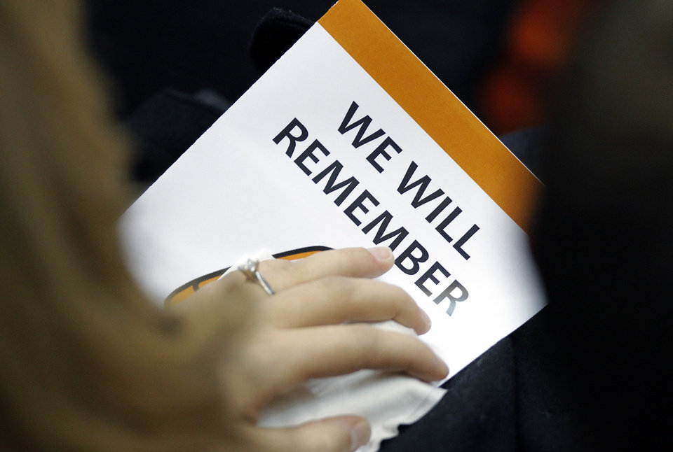 Photo - A supporter holds a memorial program during the memorial service for Oklahoma State head basketball coach Kurt Budke and assistant coach Miranda Serna at Gallagher-Iba Arena on Monday, Nov. 21, 2011 in Stillwater, Okla. The two were killed in a plane crash along with former state senator Olin Branstetter and his wife Paula while on a recruiting trip in central Arkansas last Thursday. Photo by Chris Landsberger, The Oklahoman