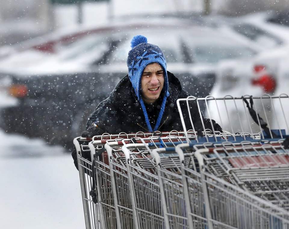 Photo - A worker pushes shopping carts through the parking lot as he returns them to the front of Crest Foods n Midwest City. Snow began falling in central Oklahoma around 7 Sunday morning, Feb. 2, 2014.   Photo by Jim Beckel, The Oklahoman