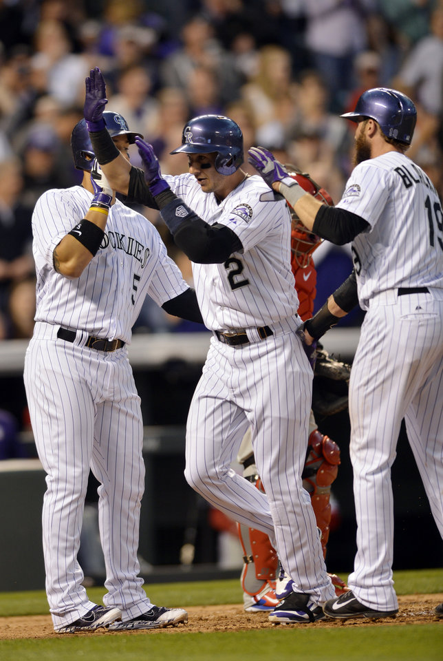 Photo - Colorado Rockies' Troy Tulowitzki (2) is congratulated by teammates Carlos Gonzalez (5) and Charlie Blackmon (19) after driving them in on a three-run home run hit off Philadelphia Phillies starting pitcher Jonathan Pettibone (44) during the second inning of a baseball game on Friday, April 18, 2014, in Denver. (AP Photo/Jack Dempsey)
