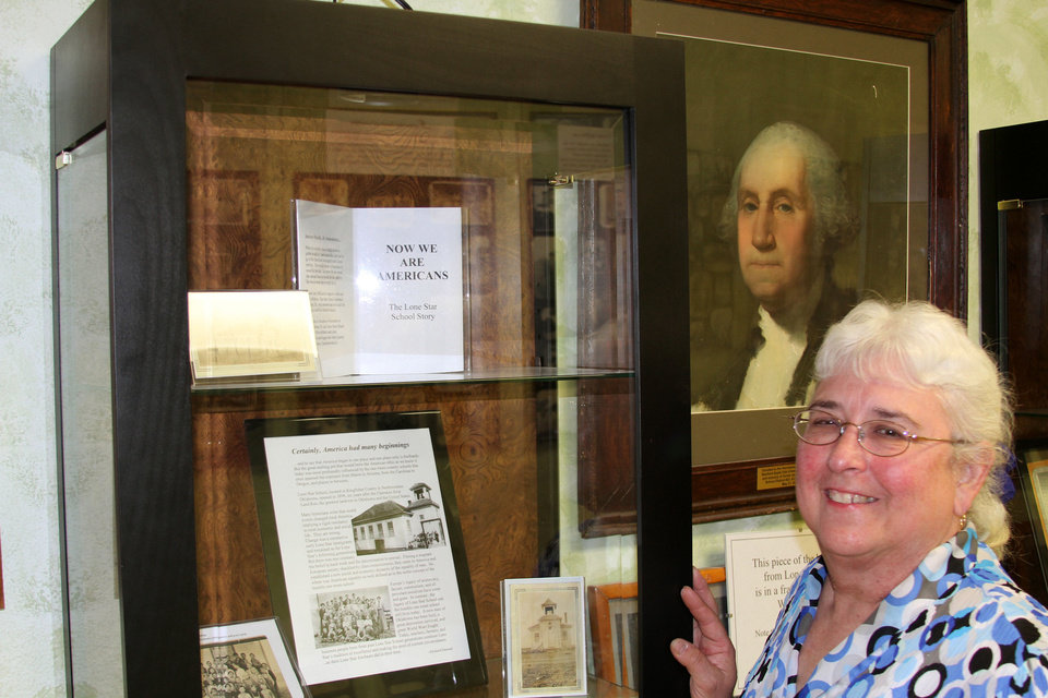 Photo - Librarian Mary Haney displays Hennessey's past in the Sam and Burla Snyder Memorial History Center. (Photo by Ron J. Jackson, Jr., Oklahoma Watch)  Ron J. Jackson, Jr.