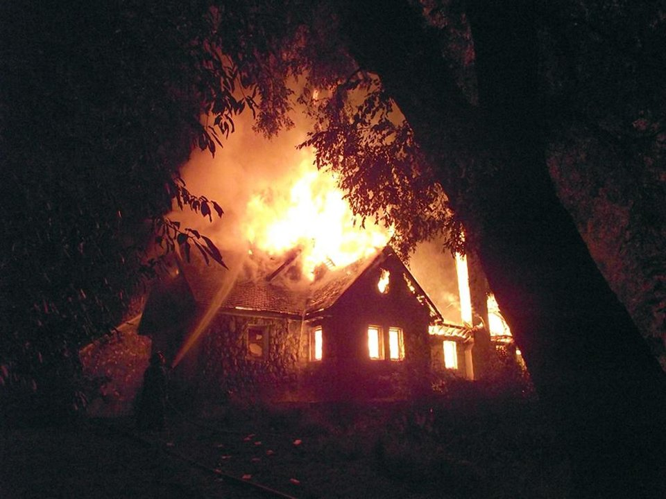 A firefighter, left, works to extinguish the flames of the home of a wealthy landowner in Temuco, Chile, Friday, Jan. 4, 2013. The elderly couple, Werner Luchsinger, 75, and wife wife Vivian McKay, whose family's vast landholdings have long been targeted by Mapuche Indians in southern Chile were killed in the arson attack early Friday while trying to defend their home. Chile's president quickly flew to the scene and announced new security measures, including the application of Chile's tough anti-terrorism law and the creation of a special police anti-terror unit backed by Chile's military. (Hector Andrade/Agenciauno)