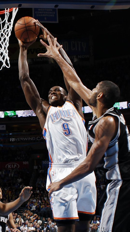 Oklahoma City\'s Serge Ibaka (9) takes the ball to the hoop against San Antonio\'s Tim Duncan (21) during an NBA basketball game between the Oklahoma City Thunder and the San Antonio Spurs at Chesapeake Energy Arena in Oklahoma City, Thursday, April 4, 2013. Photo by Nate Billings, The Oklahoman