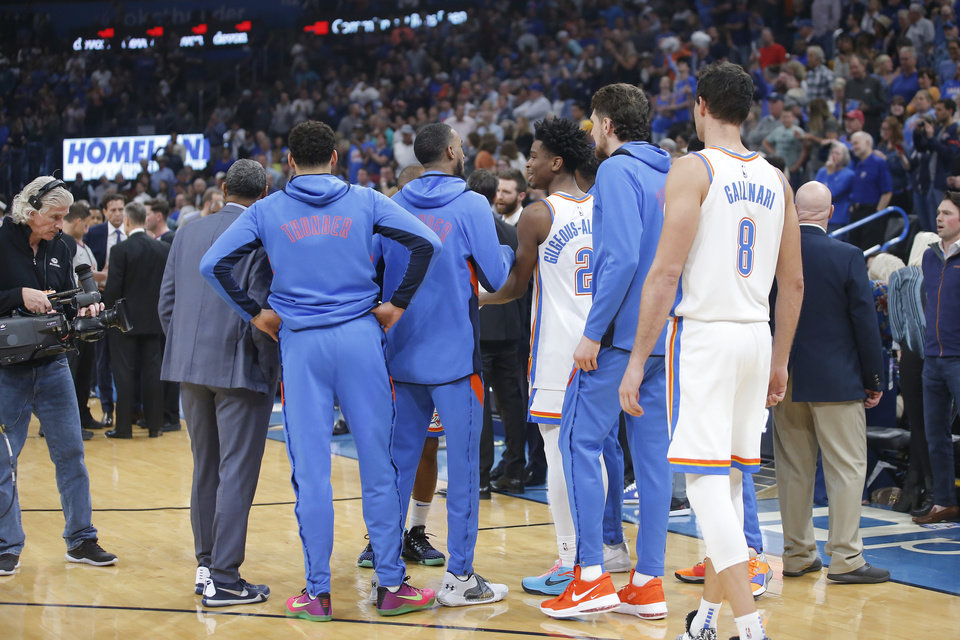 Photo - Oklahoma City players watch as officials meet before an NBA basketball game between the Oklahoma City Thunder and the Utah Jazz was postponed at Chesapeake Energy Arena in Oklahoma City, Wednesday, March 11, 2020. [Bryan Terry/The Oklahoman]