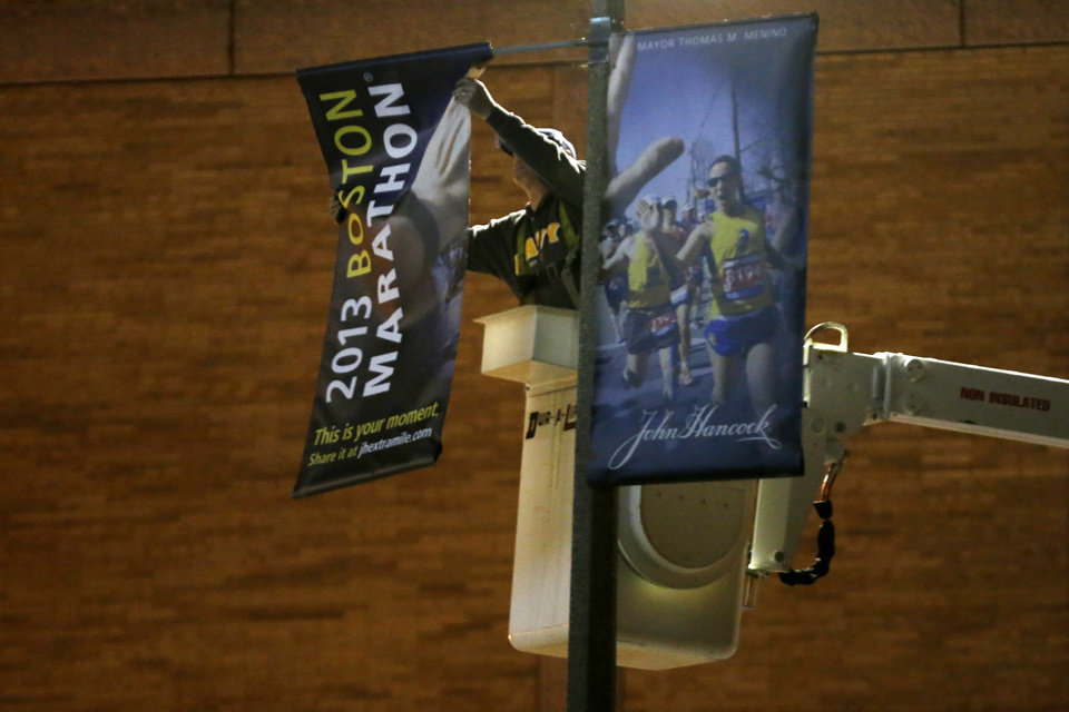 A workman removes a banner from a light pole in the vicinity of finish line of Monday's Boston Marathon explosions, which killed at least three and injured more than 140, Wednesday, April 17, 2013, in Boston. (AP Photo/Matt Rourke)