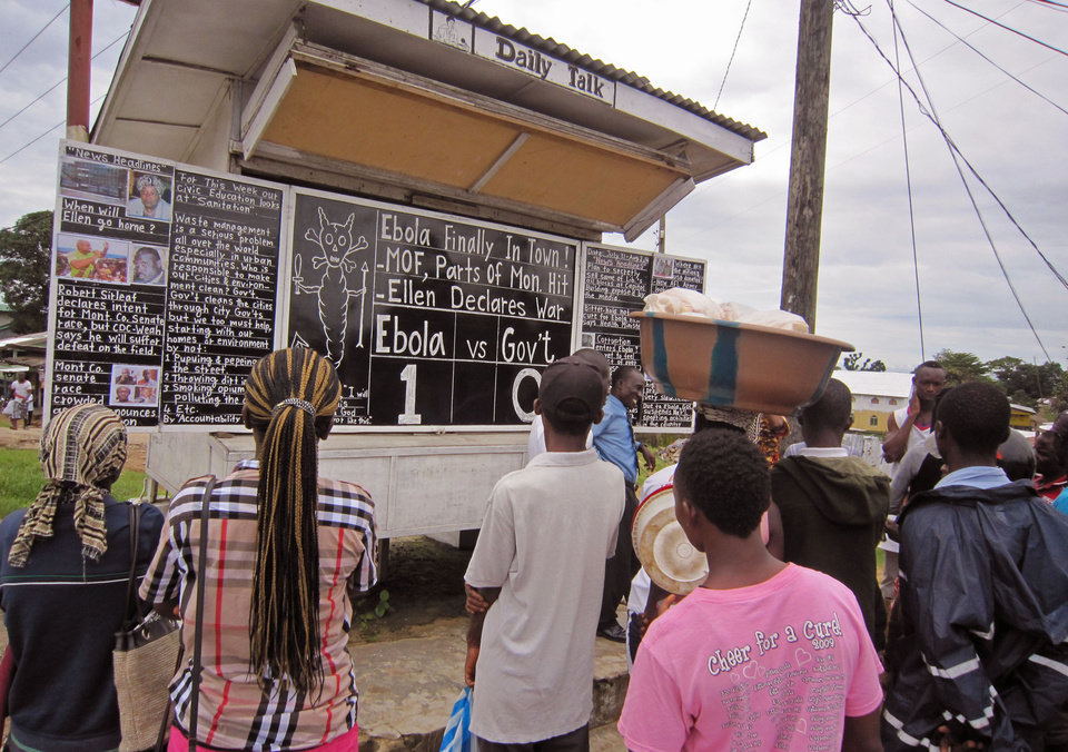 Photo - Social Commentator Alfred Sirleaf, center rear,  gives comment on current events in Liberia including the deadly Ebola virus by speaking and writhing them down on a blackboard as people gather around to listen to him in Monrovia, Liberia, Thursday, July 31, 2014. The worst recorded Ebola outbreak in history surpassed 700 deaths in West Africa as the World Health Organization on Thursday announced dozens of new fatalities. (AP Photo/Jonathan Paye-Layleh)