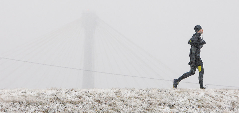 Photo - A man jogs on the levee in Alton, Ill. during a blowing snow that almost obscures the Clark Bridge in Alton, Ill. Tuesday, March 5, 2013. (AP Photo/The Telegraph, John Badman)  THE NEWS-DEMOCRAT AND THE POST-DISPATCH OUT