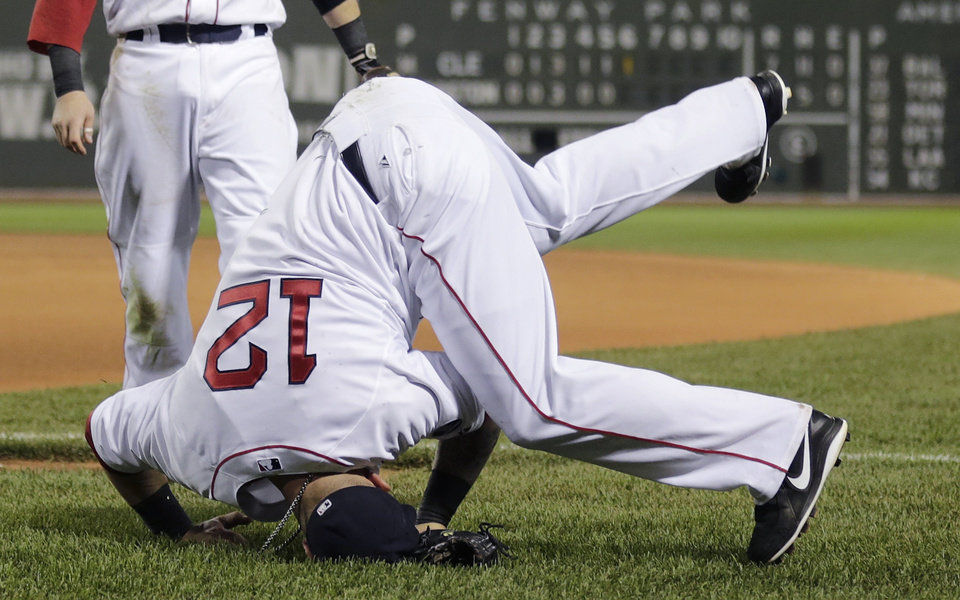 Photo - Boston Red Sox first baseman Mike Napoli (12) lands on his head while missing the catch on a foul by Cleveland Indians' Yan Gomes in the seventh inning of a baseball game at Fenway Park in Boston, Thursday, May 23, 2013. (AP Photo/Charles Krupa)