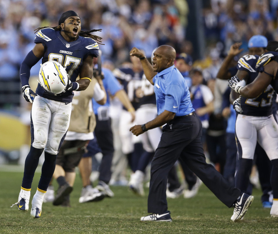 Photo - San Diego Chargers defensive back Jahleel Addae celebrates as does secondary coach Ron Milus after the Chargers' 27-24 overtime victory over the Kansas City Chiefs in an NFL football game, Sunday, Dec. 29, 2013, in San Diego. The victory put the Chargers into the playoffs.  (AP Photo/Lenny Ignelzi)