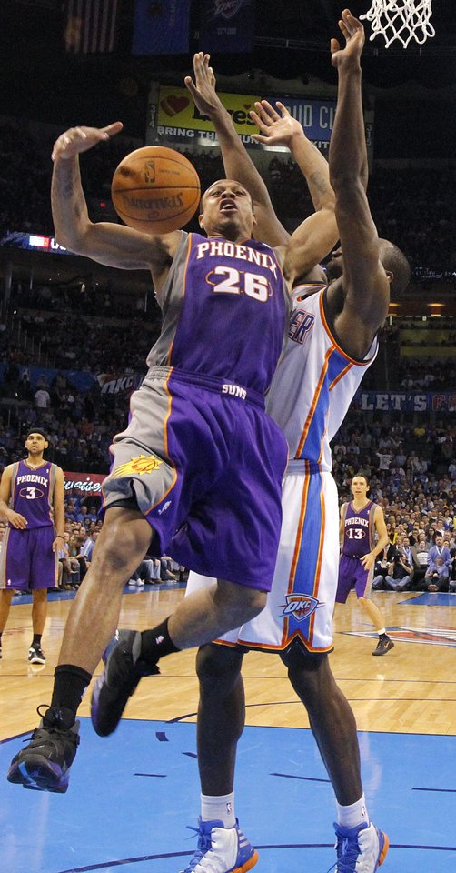Photo - Oklahoma City Thunder power forward Serge Ibaka (9) defends on Phoenix Suns shooting guard Shannon Brown (26) during the NBA basketball game between the Oklahoma City Thunder and the Phoenix Suns at the Chesapeake Energy Arena on Wednesday, March 7, 2012 in Oklahoma City, Okla.  Photo by Chris Landsberger, The Oklahoman