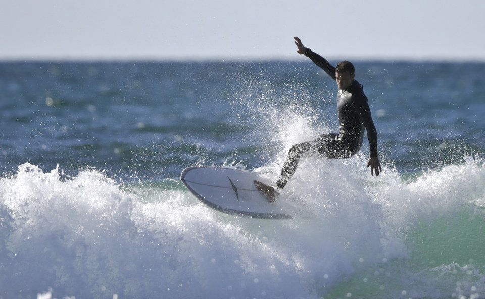 Photo - A surfer sails on top of a wave on a sunny but cold day Wednesday, Dec. 16, 2015, in Cardiff, Calif.  (AP Photo/Lenny Ignelzi)