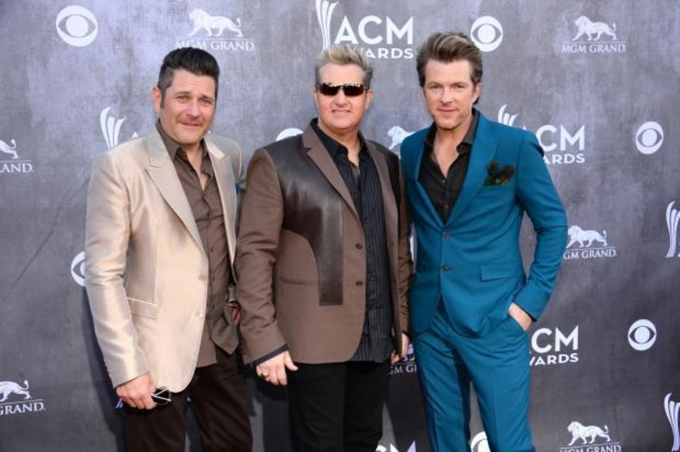 Photo -  Jay DeMarcus, and from left, Gary LeVox and Picher-bred Joe Don Rooney, of the musical group Rascal Flatts, arrive at the 49th annual Academy of Country Music Awards at the MGM Grand Garden Arena on Sunday, April 6, 2014, in Las Vegas. (AP)