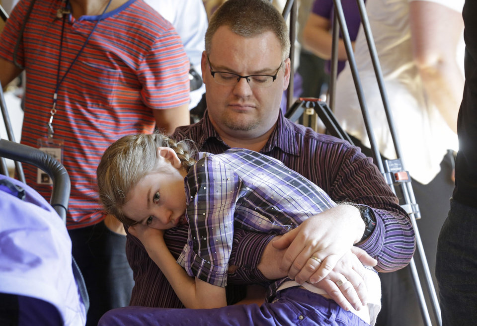 Photo - FILE - In this March 25, 2014, file photo, Marshall Christensen, of Provo, holds his daughter Jessica, 13, as they wait for the H.B 105 bill signing ceremony at the Utah State Capitol, in Salt Lake City. Utah will begin issuing registration cards Tuesday, July 8, 2014, for its limited medical marijuana program targeting adults and children with severe epilepsy.  (AP Photo/Rick Bowmer, File)