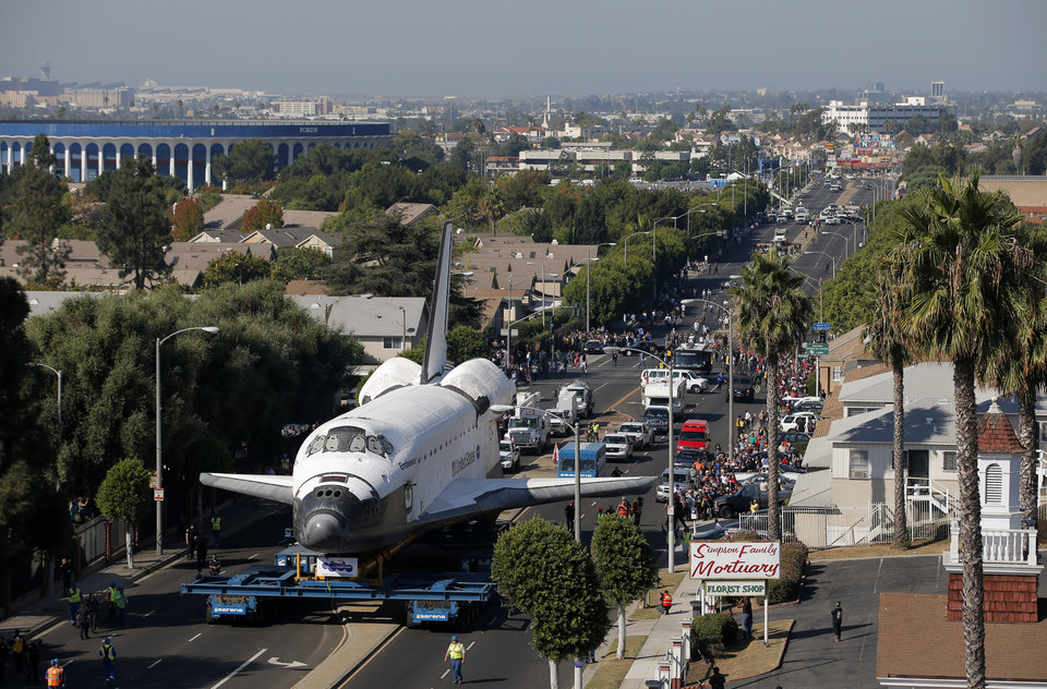 The Space Shuttle Endeavour slowly moves along city streets on a 160-wheeled carrier in Inglewood, Calif., Saturday, Oct. 13, 2012. After slowly surmounting a key obstacle, the shuttle Endeavour maintained a heading Saturday through the streets of Los Angeles toward its retirement home at a museum. (AP Photo/Jae C. Hong)