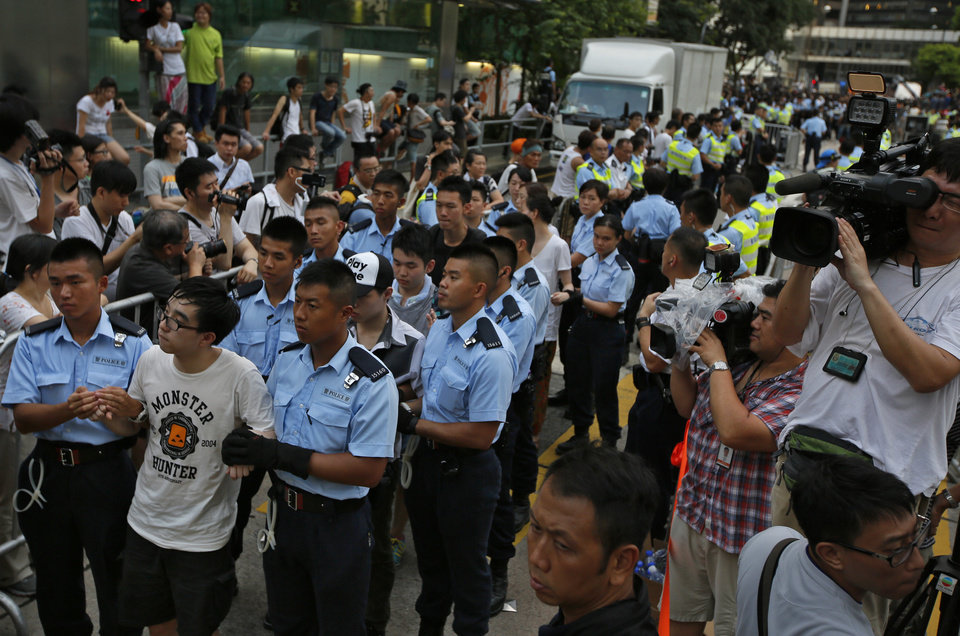 Photo - Protesters are arrested by police officers after hundreds of protesters staged a peaceful sit-ins overnight on a street in the financial district in Hong Kong Wednesday, July 2, 2014, following a huge rally to show their support for democratic reform and oppose Beijing's desire to have the final say on candidates for the chief executive's job. (AP Photo/Vincent Yu)