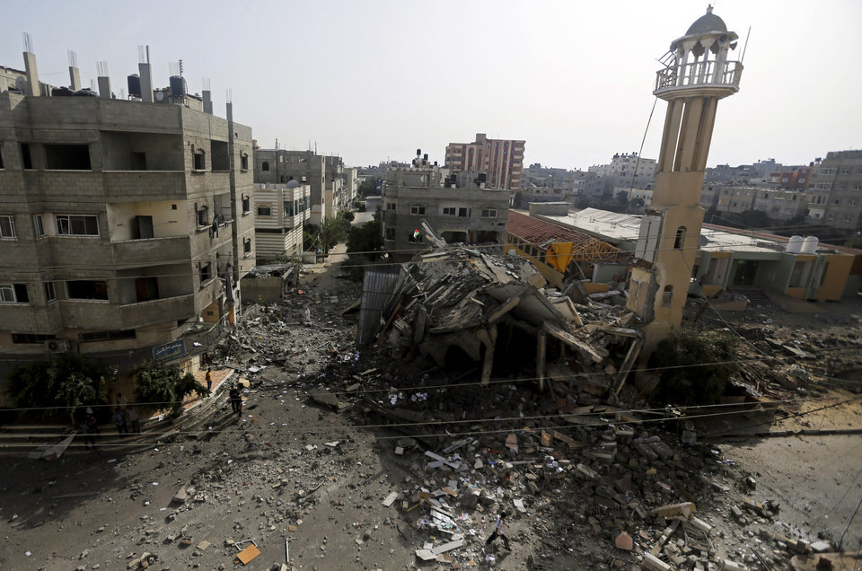 Photo - Palestinians walk around the ruins of the Al-Tawfeeq Mosque after it was hit by an overnight Israeli missile strike in the Nuseirat refugee camp, central Gaza Strip, Saturday, July 12, 2014. Israeli airstrikes targeting Hamas in Gaza hit a mosque its military says concealed the militant group's weapons, as the Palestinian death toll topped 120 Saturday in an offensive that showed no signs of slowing down. (AP Photo/Hatem Moussa)