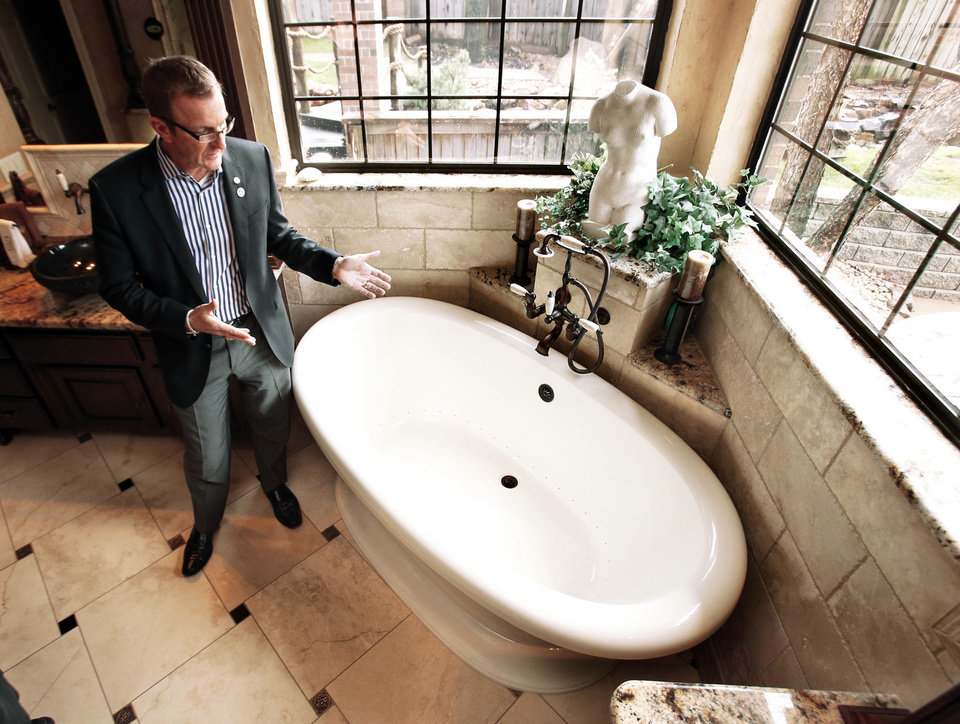 Builder Kurt Dinnes shows the master bath at his family's home in the Crystal Lakes neighborhood in Norman.