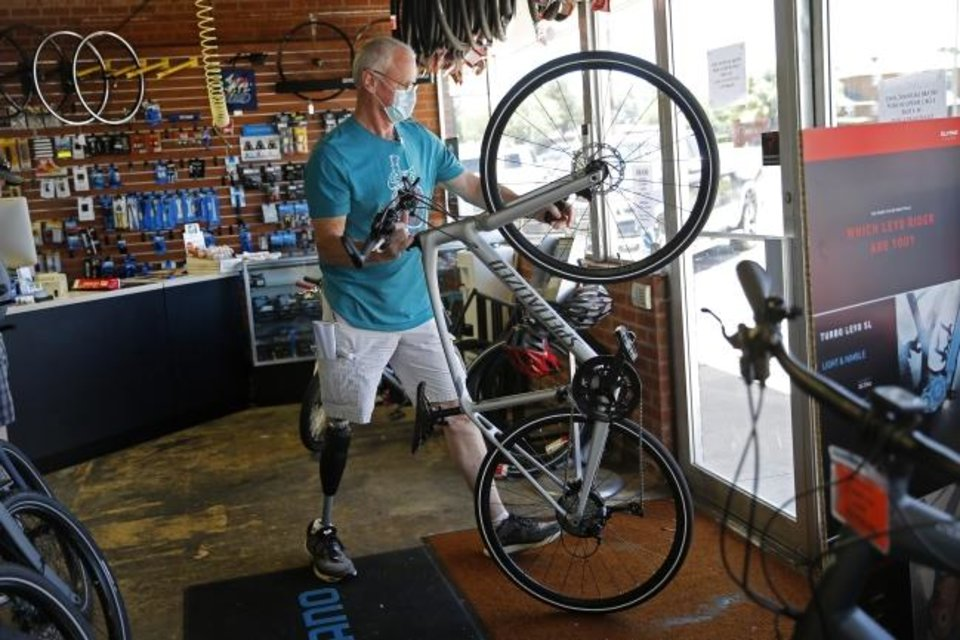 Photo -  Owner Steve Gooden takes a bike outside at Wheeler Dealer Bicycle Shop in Oklahoma City on Friday. [Bryan Terry/The Oklahoman]