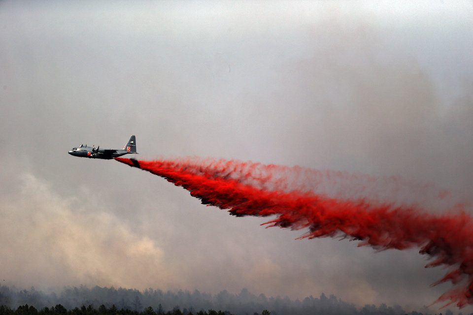 Photo - A U.S. Army C-130 makes a slurry drop on a wildfire in the Black Forest area north of Colorado Springs, Colo., on Wednesday, June 12, 2013. As many as 50 homes were destroyed by the fire on Tuesday. (AP Photo/Ed Andrieski)