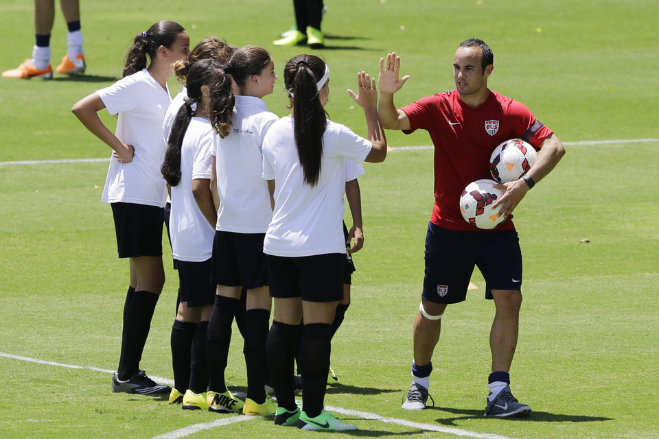 Photo - United States' Landon Donovan high fives young players who will attend a program coined
