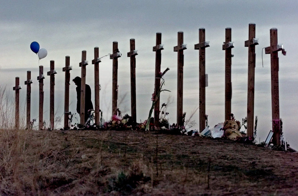 FILE - This April 28, 1999 file photo shows an unidentified woman with15 crosses posted on a hill above Columbine High School in Littleton, Colo. Wednesday, April 28, 1999 in remembrance of the 15 people who died during a school shooting on April 20. Sony Electronics and the Nielsen television research company collaborated on a survey ranking TV's most memorable moments. Other TV events include, the Sept. 11 attacks in 2001, Hurricane Katrina in 2005, the O.J. Simpson murder trial verdict in 1995 and the death of Osama bin Laden in 2011. (AP Photo/Eric Gay, file) ORG XMIT: NYET124