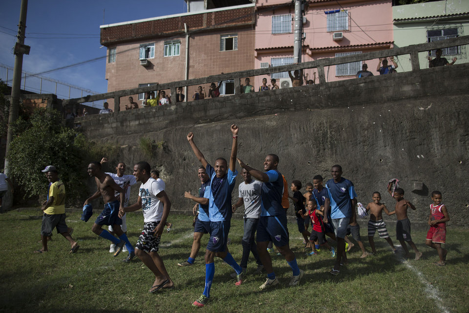 Photo - In this May 03, 2014 photo, players from the Escada Azul team celebrate classifying for the semi-finals of an amateur soccer tournament in the Mangueira shantytown of Rio de Janeiro, Brazil. The high costs of preparing for the 2013 Confederations Cup and upcoming World Cup, blamed in part by the late rush to get projects done, ignited a wave of public criticism from a population already tired of poor public services and widespread corruption and yet, in Brazil, soccer is a unifying force. (AP Photo/Leo Correa)