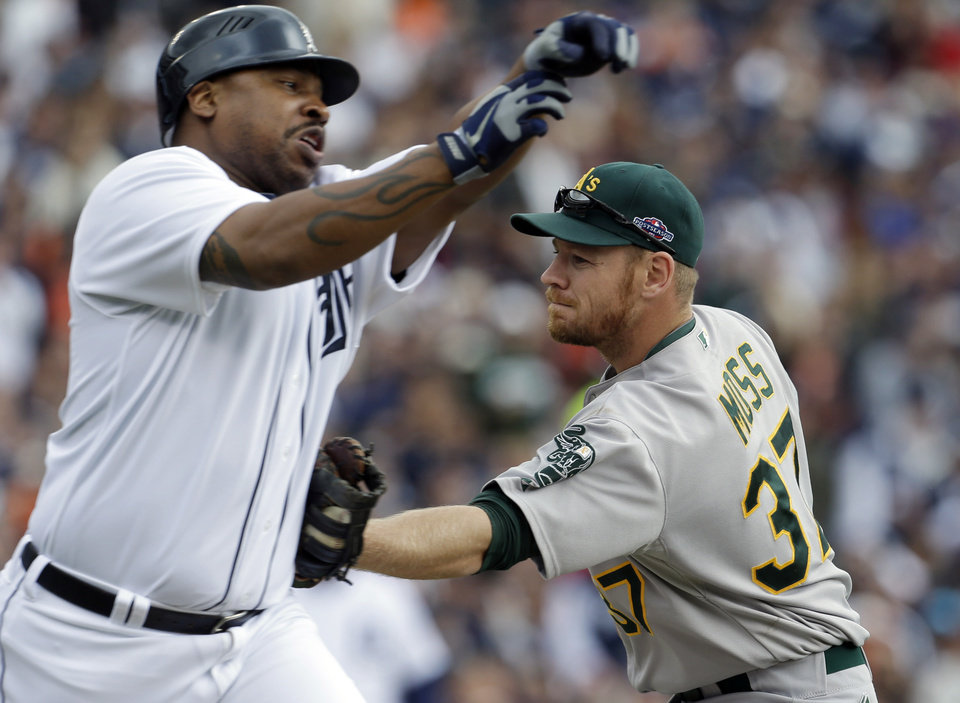 Photo -   Detroit Tigers designated hitter Delmon Young, left, is tagged out by Oakland Athletics first baseman Brandon Moss (37), allowing teammate Miguel Cabrera to score from third, during the third inning of Game 2 of the American League division baseball series on Sunday, Oct. 7, 2012, in Detroit. (AP Photo/Paul Sancya)