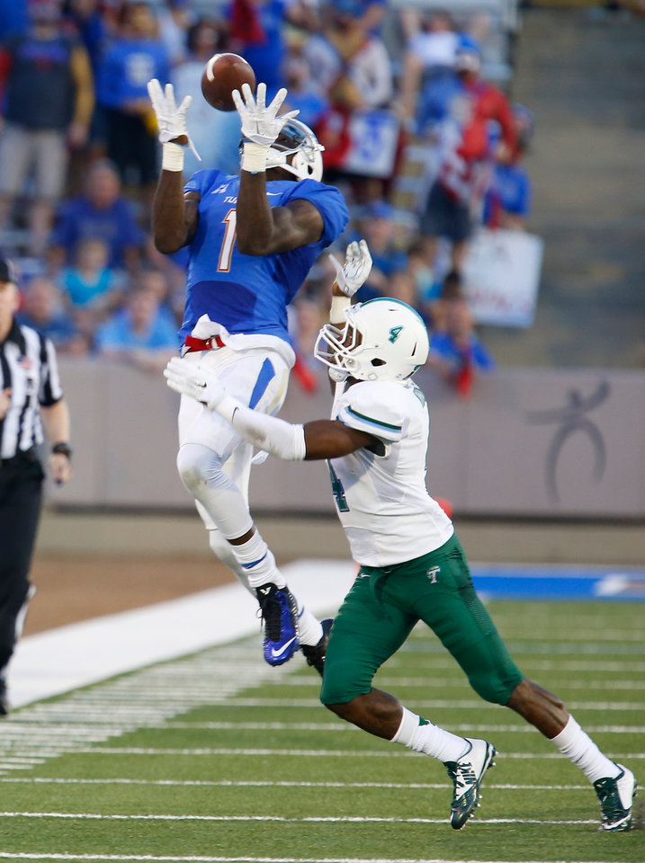 Photo - Tulsa's Keyarris Garrett (1) pulls down a long pass as Tulane's (4) Taurean Nixon watches during the first half  of an NCAA college football game on Thursday, Aug. 28, 2014, in Tulsa, Okla. (AP Photo/Tulsa World, Tom Gilbert) ONLINE OUT; KOTV OUT; KJRH OUT; KTUL OUT; KOKI OUT; KQCW OUT; KDOR OUT; TULSA OUT; TULSA ONLINE OUT