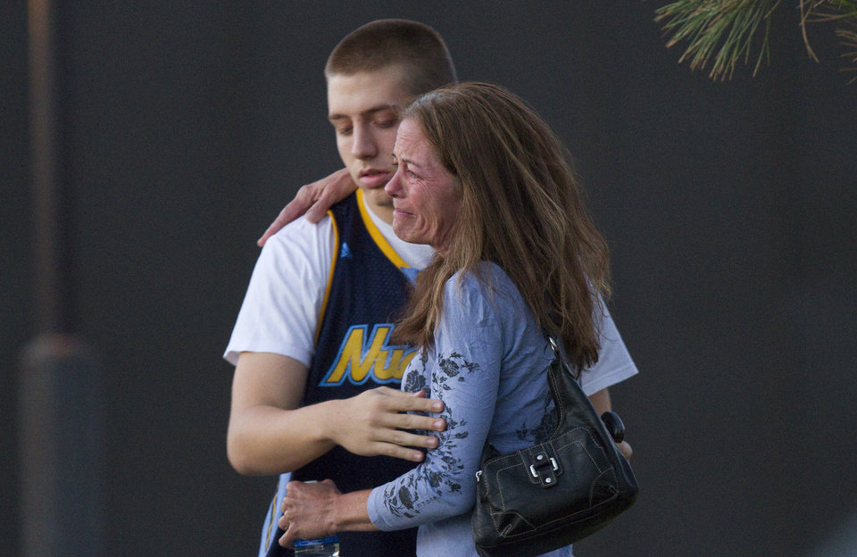 Photo - Eyewitness Jacob Stevens, 18, hugs his mother Tammi Stevens after being interview by police outside Gateway High School where witnesses were brought for questioning Friday, July 20, 2012 in Aurora, Colo.  A gunman wearing a gas mask set off an unknown gas and fired into the crowded movie theater killing 12 people and injuring at least 50 others, authorities said. (AP Photo/Barry Gutierrez) ORG XMIT: COBG107