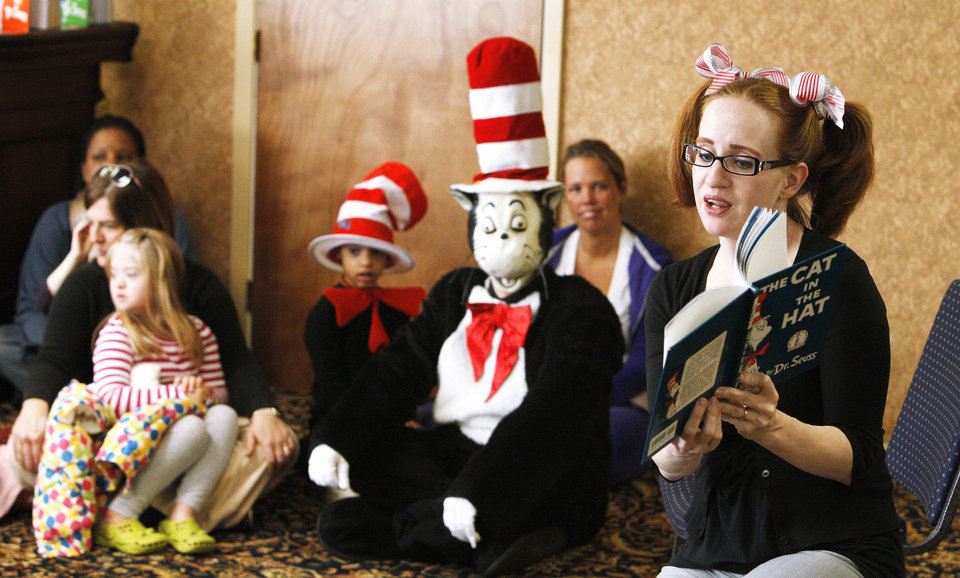 Photo - The Cat in the Hat looks on as Kacie Webster reads to students from Positive Tomorrows and Special Care at The Fountains at Canterbury as part of Read Across America Day. The event is held close to the birthday of Dr. Seuss. The National Education Association estimates that about 45 million people nationwide picked up a book to mark the occasion. Photo by Paul B. Southerland,  The Oklahoman