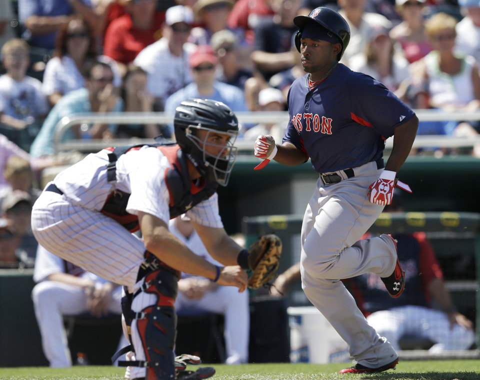 Photo - Boston Red Sox's Jackie Bradley, Jr. scores on a single by Dustin Pedroia as Minnesota Twins catcher Eric Fryer awaits the throw in from the outfield in the sixth inning of an exhibition spring training baseball game in Fort Myers, Fla., Friday, March 29, 2013. (AP Photo/Elise Amendola)