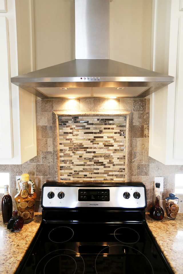 Photo - A detailed tile backsplash adds texture and style to the kitchen of the TimberCraft model home at 8440 NW 142.