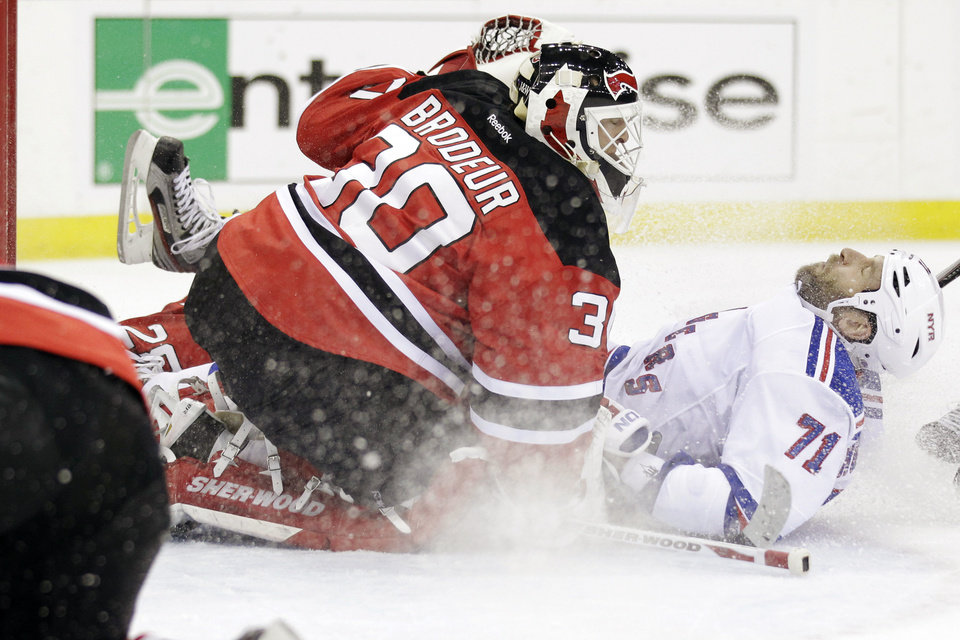 Photo -   New York Rangers' Mike Rupp, right, falls back while attacking against New Jersey Devils goalie Martin Brodeur during the first period of Game 4 of an NHL hockey Stanley Cup Eastern Conference final playoff series, Monday, May 21, 2012, in Newark, N.J. (AP Photo/Julio Cortez)