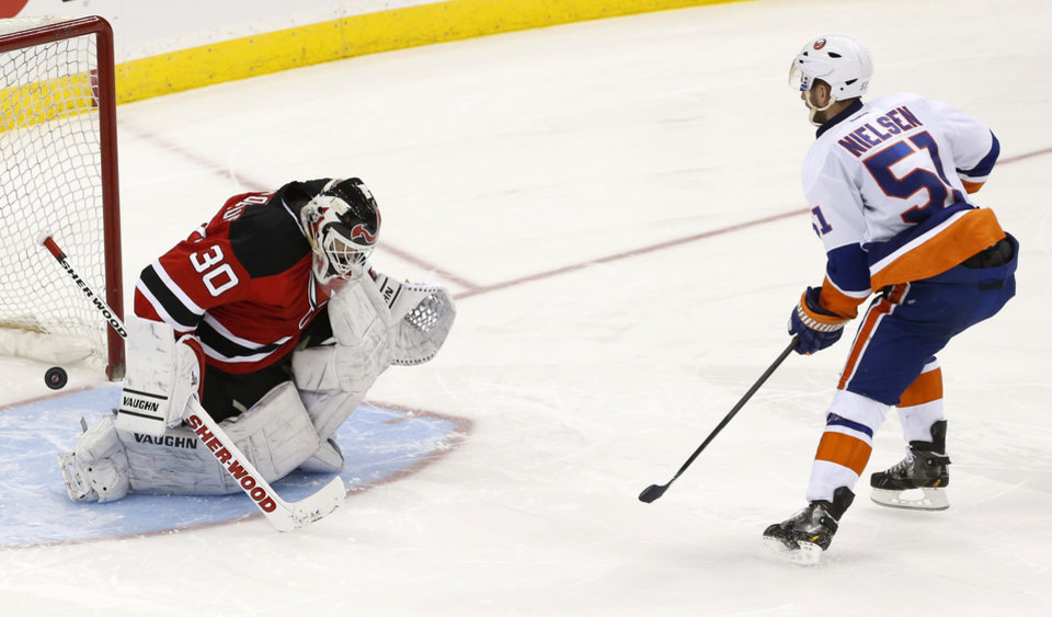 Photo - New York Islanders center Frans Nielsen (51), of Denmark, scores a goal against New Jersey Devils goalie Martin Brodeur (30) during a shootout in an NHL hockey game, Friday, April 11, 2014, in Newark, N.J. The Islanders won 3-2. (AP Photo/Julio Cortez)