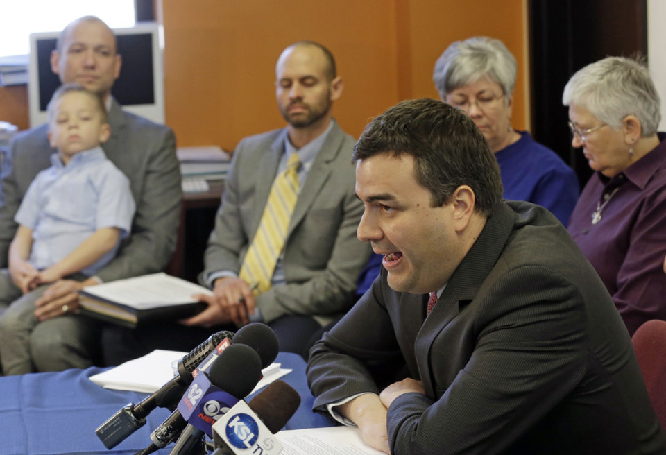 Photo - Attorney John Mejia, with the American Civil Liberties Union, foreground, speaks during a news conference as plaintiffs, in the back ground, look on Tuesday, Jan. 21, 2014, in Salt Lake City. The American Civil Liberties Union has sued the state of Utah over the issue of gay marriage, saying the official decision to stop granting benefits for newly married same-sex couples has created wrenching uncertainty. The lawsuit filed Tuesday says the state has put hundreds of gay and lesbian couples in legal limbo and prevented them from getting key protections for themselves and their children. (AP Photo/Rick Bowmer)