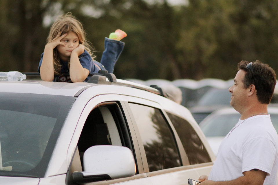 Photo - Steve Gales talks with his daughter Josie Gales, 8, as she waits on top of their car for the movie to start at the Airline Drive-in movie theater in Ponca City Thursday, August 14, 2014. Photo by Doug Hoke, The Oklahoman