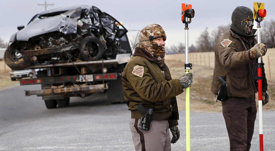 Photo - The vehicle driven by  Burns Flat police officer Kristian Willhight, 36, is removed from the crash site as two OHP accident investigators gather information. A Burns Flat police officer and an undersheriff for the Washita County Sheriff's Department died in a car crash on Thursday, Jan. 23, 2014, at a rural intersection about one mile south of Dill City.  According to OHP spokesman, the lawmen became involved in a high-speed pursuit  when a Washita County man fled as the undersheriff approached him to serve a felony warrant Thursday morning.  That same suspect died about the same time in another crash about three miles east of the location where the law officers collided. Dill City is located 75 miles west of Oklahoma City. Photo by Jim Beckel, The Oklahoman