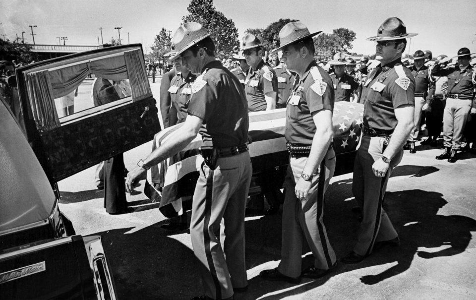 Photo - Oklahoma Highway Patrol troopers lead the body of Lt. Pat Grimes into a hearse after his funeral in Moore on May 30, 1978. Grimes and two other troopers were killed in a gun battle with two escapees from the Oklahoma State Penitentiary on May 26, 1978.  Photo by Roger Klock, The Oklahoman. Copy of a print from The Oklahoman Archive, Tuesday, Dec. 6, 2011.