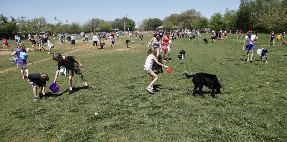 Photo - People and their dogs scour the field looking for eggs during the first Hound Hunt, an Easter Egg hunt for dogs inside the dog park at Bick ham-Rudkin Park in Edmond Sunday April 1, 2012. The eggs are filled with dog treats. Photo by Doug Hoke, The Oklahoman