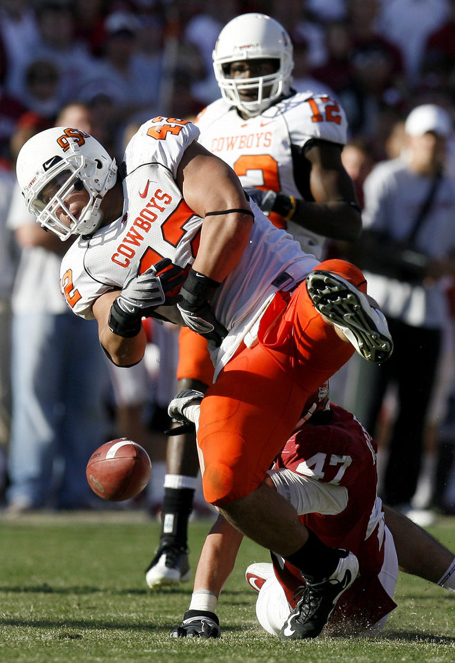 Photo - OSU's Justin Gent (42) fumbles after recovering an Oklahoma fumble during the second half of the Bedlam college football game between the University of Oklahoma Sooners (OU) and the Oklahoma State University Cowboys (OSU) at the Gaylord Family-Oklahoma Memorial Stadium on Saturday, Nov. 28, 2009, in Norman, Okla. Photo by Sarah Phipps, The Oklahoman