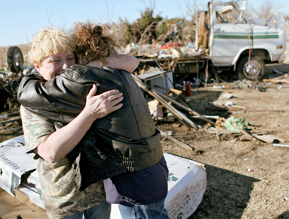 Photo - Margie Hughes, left, gets a hug from her sister Neda Wilson as they look at Margie's destroyed home Wednesday in Lone Grove.  Photo By John Clanton, The Oklahoman
