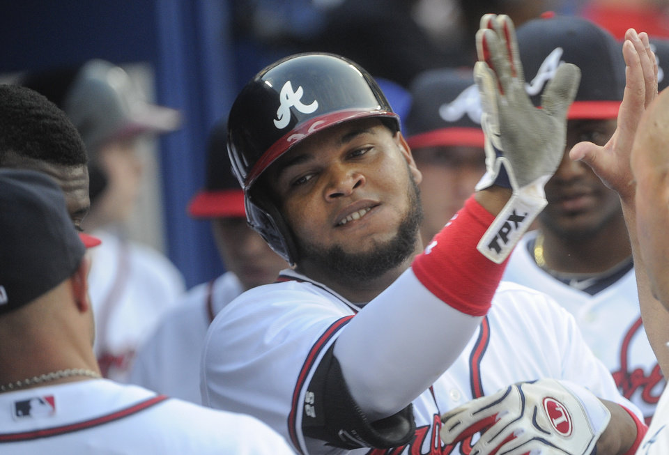 Atlanta Braves' Juan Francisco celebrates in the dugout after hitting a home run against the Kansas City Royals during the second inning of a baseball game, Tuesday, April 16, 2013, in Atlanta. (AP Photo/John Amis)