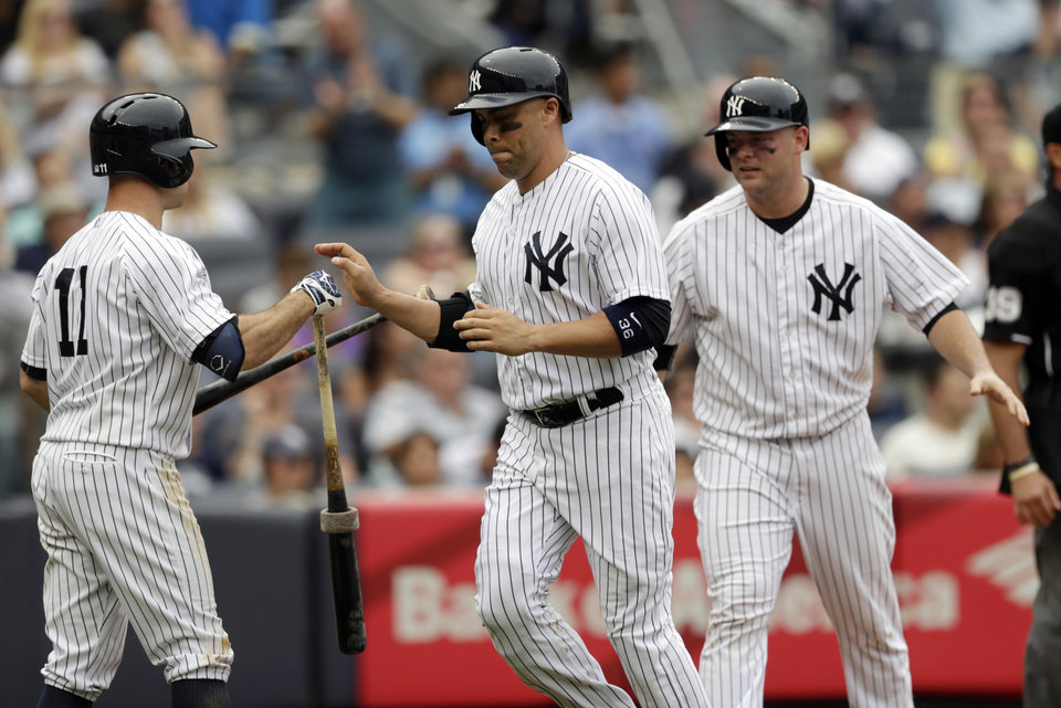 Photo - New York Yankees' Carlos Beltran, center, and Brian McCann, right, are congratulated by teammate Brett Gardner, left, after they scored on an RBI single by Kelly Johnson during the sixth inning of a baseball game against the Cincinnati Reds, Saturday, July 19, 2014, at Yankee Stadium in New York. (AP Photo/Julio Cortez)