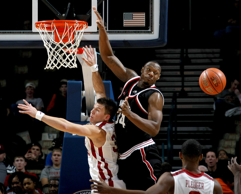 Photo - OU's Cade Davis fights for the ball with Cincinnati's Yancy Gates during the All-College Classic basketball game between the University of Oklahoma and Cincinnati at the Oklahoma City Arena on Saturday, December 18,  2010.   Photo by Bryan Terry, The Oklahoman