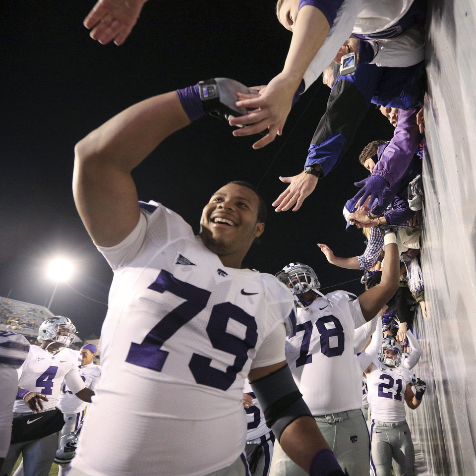 Photo -   Players from Kansas State, including Keenan Taylor (79), celebrate their victory with fans following an NCAA college football game against West Virginia in Morgantown, W.Va., Saturday, Oct. 20, 2012. Kansas State won 55-14. (AP Photo/Christopher Jackson)