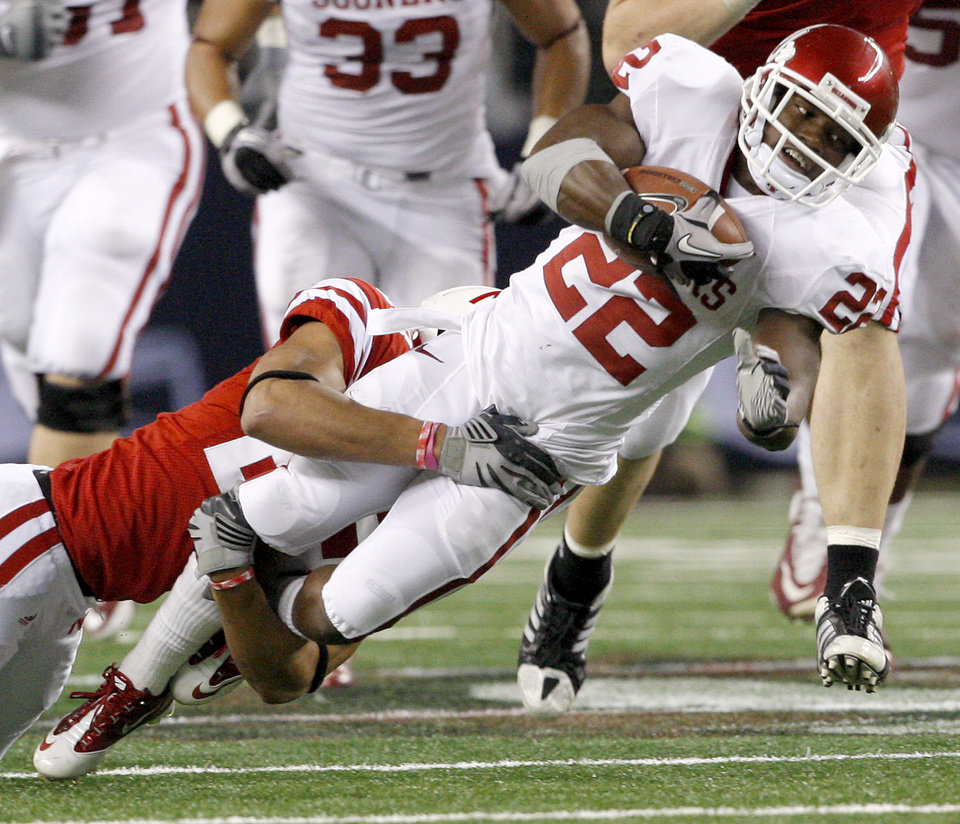 Photo - OU's Roy Finch is brought down by Nebraska's Eric Hagg during the Big 12 football championship game between the University of Oklahoma Sooners (OU) and the University of Nebraska Cornhuskers (NU) at Cowboys Stadium on Saturday, Dec. 4, 2010, in Arlington, Texas.  Photo by Bryan Terry, The Oklahoman