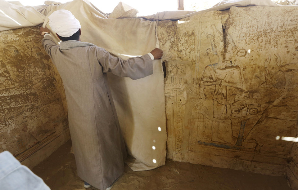 """Photo - An Egyptian archeology worker covers  limestones at a newly-discovered tomb dating back to around 1100 B.C. at the Saqqara archaeological site, 30 kilometers (19 miles) south of Cairo, Egypt, Thursday, May 8, 2014. Antiquities Minister Mohamed Ibrahim said Thursday that the tomb belongs to a guard of the army archives and royal messenger to foreign countries. Ibrahim says the Cairo University Faculty of Archaeology's discovery at Saqqara adds """"a chapter to our knowledge about the history of Saqqara."""" Saqqara was the necropolis for the ancient Egyptian city of Memphis and site of the oldest known pyramid in Egypt.(AP Photo/Amr Nabil)"""