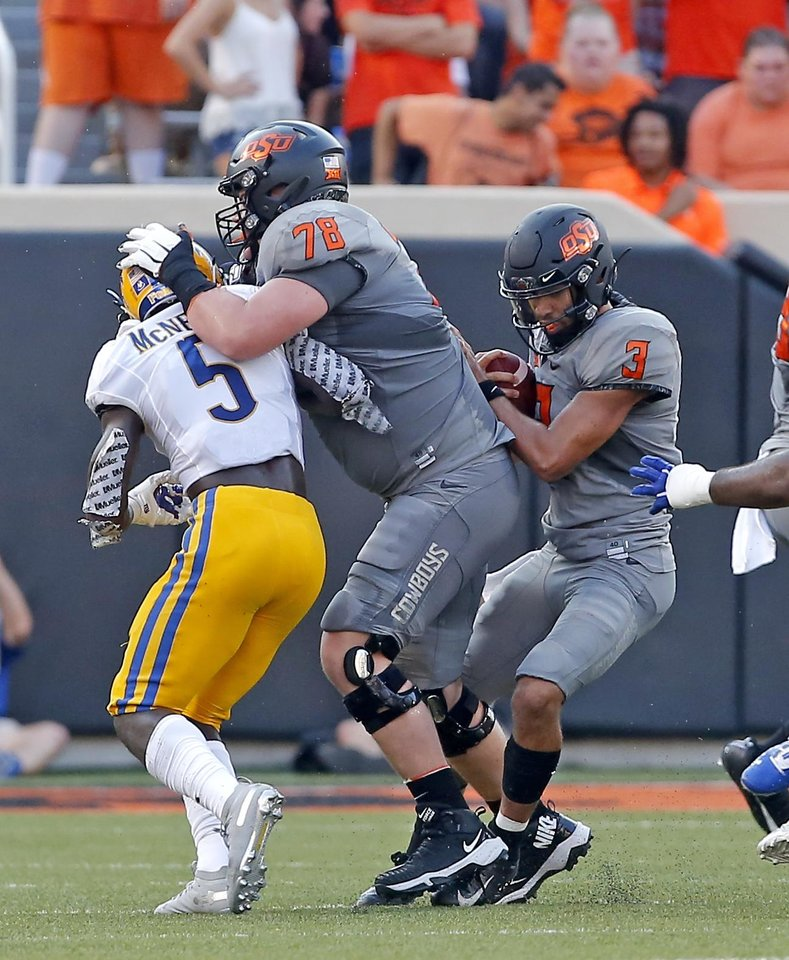 Photo - Oklahoma State's Bryce Bray (78) blocks McNeese State's Jovon Burriss (5) as Spencer Sanders (3) rushes during the college football game between the Oklahoma State Cowboys and the McNeese State Cowboys at Boone Pickens Stadium in Stillwater, Okla., Saturday, Sept. 7, 2019. [Sarah Phipps/The Oklahoman]
