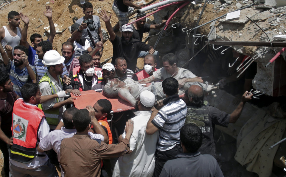 Photo - Palestinian rescue workers and civilians remove a lifeless body from the rubble of a house destroyed by an Israeli missile strike, in Gaza City, Monday, July 21, 2014. On Sunday, the first major ground battle in two weeks of Israel-Hamas fighting exacted a steep price, killing scores of Palestinians and over a dozen Israeli soldiers and forcing thousands of terrified Palestinian civilians to flee their devastated Shijaiyah neighborhood, which Israel says is a major source for rocket fire against its civilians. (AP Photo/Khalil Hamra)